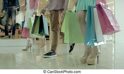 Shopping at Weekend - Dynamic side view of three...