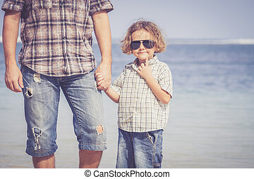 Father and son playing on the beach at the day time Concept...