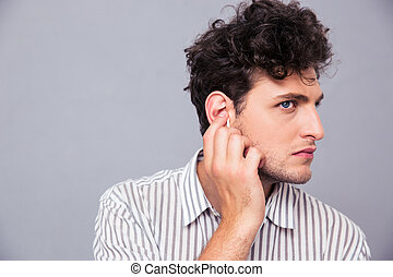 Man with headphones over gray - Closeup portrait of a young...