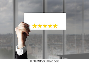 hand holding up small sign five rating stars - businessmans...