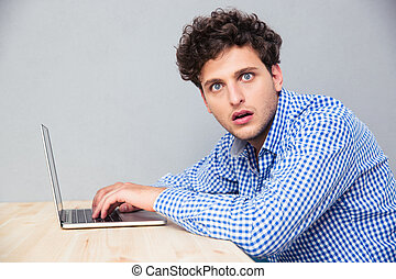 Shocked man sitting at the table with laptop - Side view...