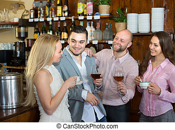 Young adults in bar - Group of smiling young adults hanging...