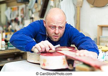 Craftsman holding unfinished guitar - Portrait of...