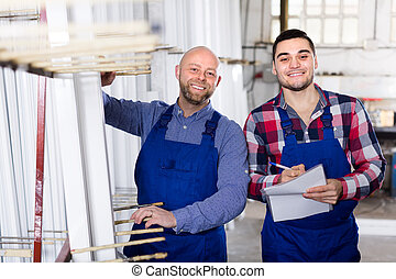 Two smiling workmen at factory - Smiling production workers...