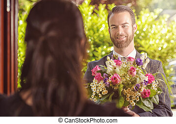 Handsome Guy Gives Fresh Flowers to his Girlfriend -...