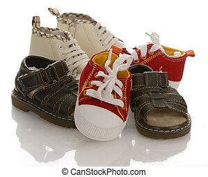 pile of baby or infant shoes with reflection on white...