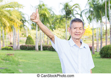 Asian senior man giving thumb up in the park