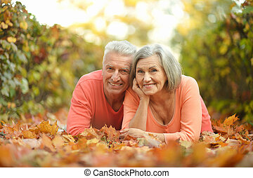 Mature couple lying on leaves in the autumn park