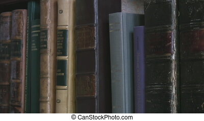 Shelf filled with old valuable books - Panning along a shelf...