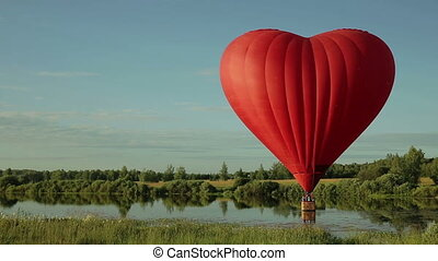 Hot air balloon flying over lake - Hot air balloon in the...