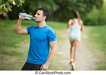 Young man drinking water outdoors