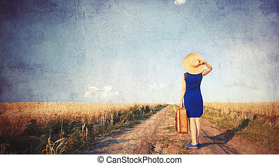 Brunette girl with suitcase at countryside road