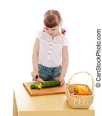 Adorable little blonde girl cut with a knife cucumber...