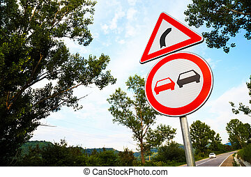 No overtake and three-cornered right turn sign on a highway...