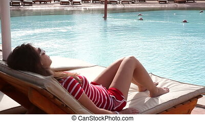 beautiful woman lying on a lounger by the pool