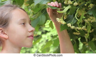 Girl smells linden flowers