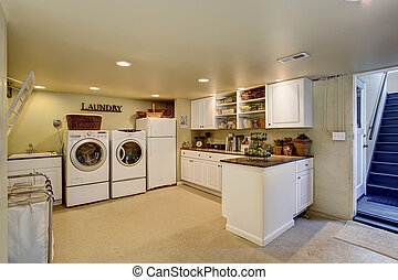 Large laundry room with appliances and cabinets.