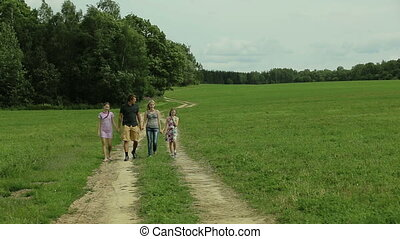 Happy family walking country road holding hands