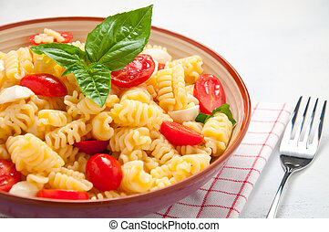 Pasta salad with tomatoes, olives, mozzarella and basil