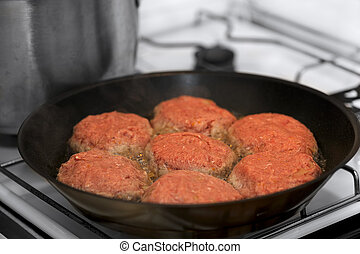 frying meat rissoles in black griddle