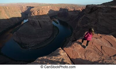 Girl Hiker Standing at the edge of Horseshoe Bend Page Arizona