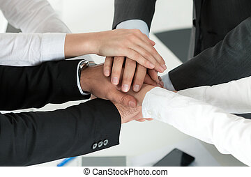 Business team showing unity with putting their hands...