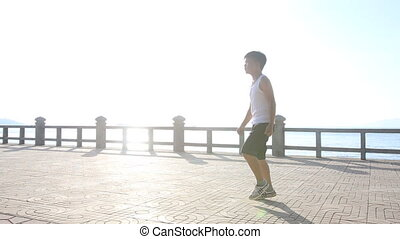 vietnamese boy does morning exercises on embankment at dawn...