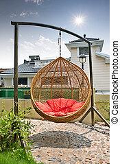 rattan hanging chair in garden