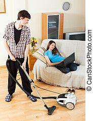 Man cleaning while wife lying with notebook - Man cleaning...