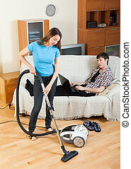 Girl cleaning with vaccuumcleaner at home while young man...
