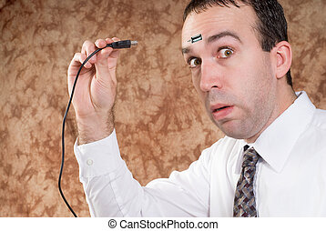 Data Transfer - A man about to plug a USB cable into his...