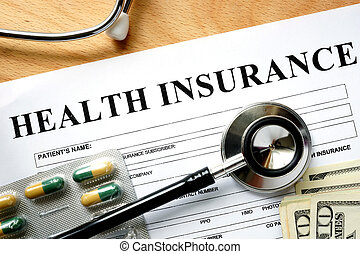 Health insurance form with stethoscope and pills