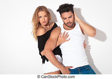 Blonde casual woman embracing her boyfriend while he is...