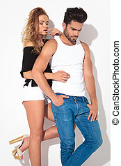 Blonde woman holding one leg up while her lover is looking...