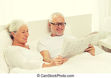 happy senior couple with newspaper in bed - family, bedtime,...