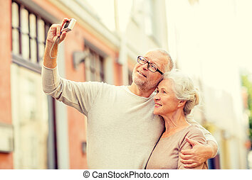 senior couple photographing on city street - age, tourism,...