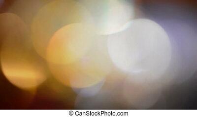 Moving colorful defocused lights dark background.