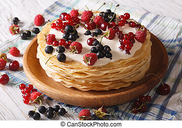 Pile of crepes with berries close-up on a plate. horizontal