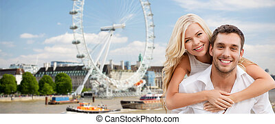 happy couple hugging over london eye ferry wheel - summer...