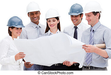 Multi-ethnic group of architects wearing hardhats against a...