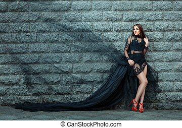 Girl in a long black dress standing near the wall.