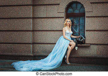 Blonde girl in a blue long dress Nearby sits the fox