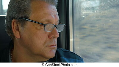 Senior man travelling by train - Senior man in glasses looks...