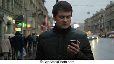Man using smartphone on the street - Adult man in the jacket...