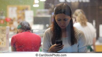 Young brunette girl using smartphone in the cafe - View...