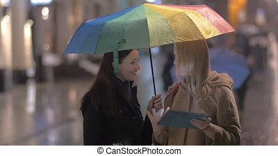 Women talking on the street on rainy day - Two young women...