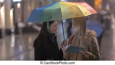Women talking on the street on rainy day