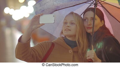 Two women friends making selfie with umbrella on rainy day