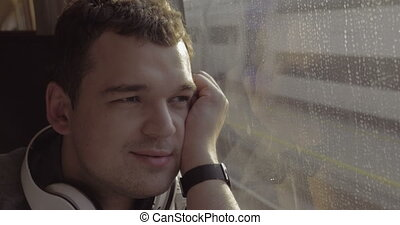Man traveling by train and enjoying outside view - Young man...