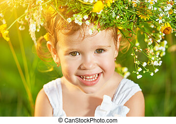 funny happy baby child girl in a wreath on nature laughing in summer
